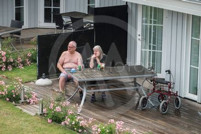 Ett äldre par sitter ute och dricker öl, Danmark.