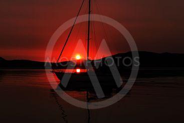 Crimson seascape sunrise with a Yacht silhouette.