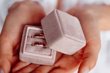 wedding rings in a pink box in the hands of bride.
