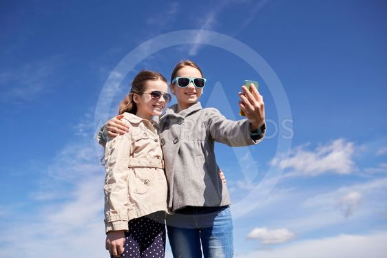 happy girls with smartphone taking selfie outdoors