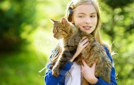 Cute little girl with her cat on sunny autumn day....