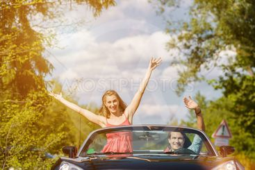 Young couple with cabriolet car in spring