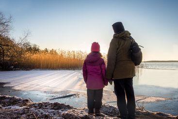 Kvinna med barn ser mot vinter solnedgång vid Mälaren.