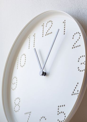 light falls on white wall clock with perforated numbers