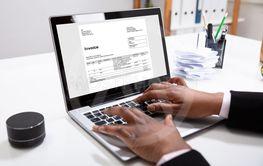 Businesswoman Checking Invoice On Laptop Near Bills On Desk