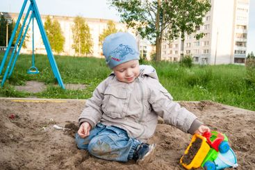 A fair-haired boy of three years in a blue hat and...