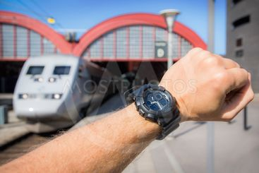 Är tåget i tid? En arm med en klocka med ett SJ X2000-tåg...