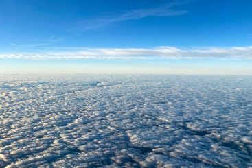 An aerial view from an airplane window of clouds with...