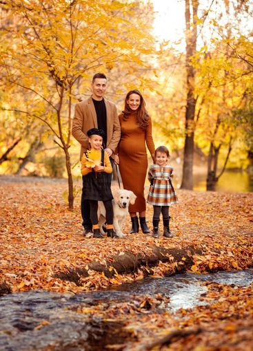 family with Retriever walking in autumn Park.