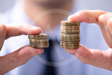 Man Comparing Two Coin Stacks