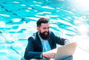 Happy businessman in suit with laptop in swimming pool....