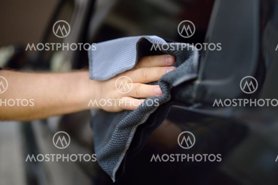 A mature man cleans his car with rag. Driver washes the...