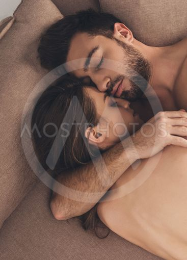 beautiful young naked couple sleeping together in bed