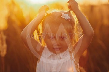 A lovely little smiling girl in a wreath of chamomiles in...