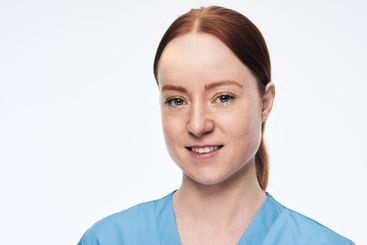 portrait of female nurse looking at camera smiling