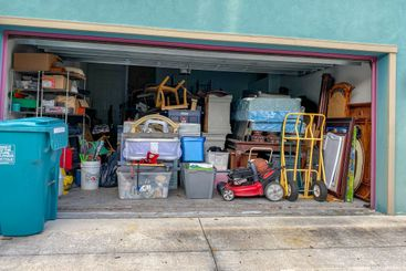 An unorganized garage filled with a lot of stuff in a...