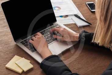 Partial view of woman typing on laptop keyboard