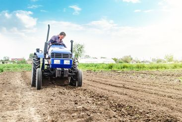 Farmer is processing soil on a tractor. Soil milling,...