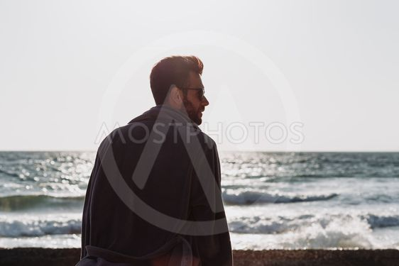 Young man in a bathrobe on the beach in sunset