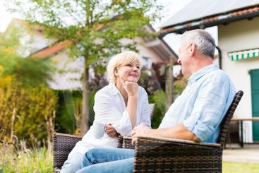 Senior man and woman sitting in front of house