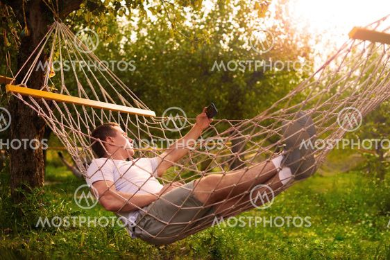 man take selfie and relax in hammock in forest in sunny...
