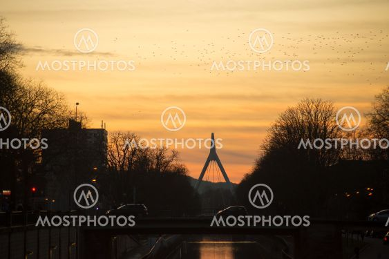 panorama with silhouette of suspended bridge under the...