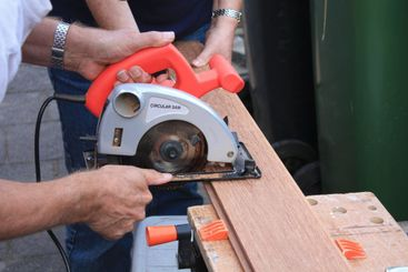 construction worker cutting wood with circular saw