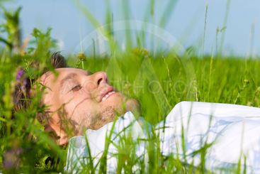 Man laying on a lawn and is dreaming