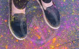 Legs of a person wearing shoes with Holi powder
