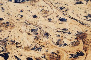 Crude oil spill on beach.