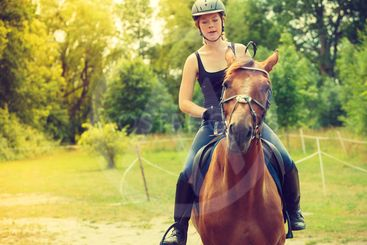 Jockey girl doing horse riding on countryside meadow