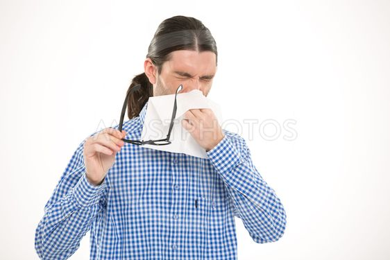 Young handsome man sneezing and using handkerchief