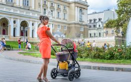 Stylish mother pushing her baby in a pram