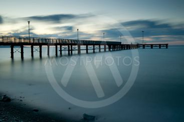 Seascape with jetty during a dramatic cloudy sunset