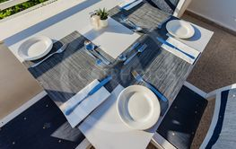 Table set with dishes for dinner on the veranda.