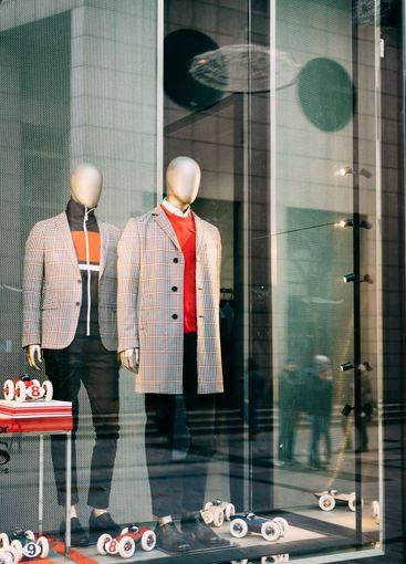 Two mannequins in the shop window of men's clothing,...