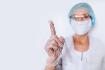 Elderly mature woman doctor or nurse raised finger in a...