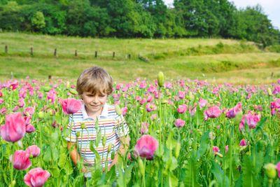 Cute happy little blond child in blooming poppy field