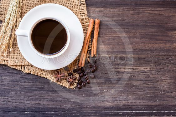 Cup of coffee and ears on dark wooden table background.