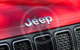 logo on red jeep front parked in the street