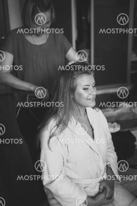 portrait of hairstylist preparing happy bride to wedding...