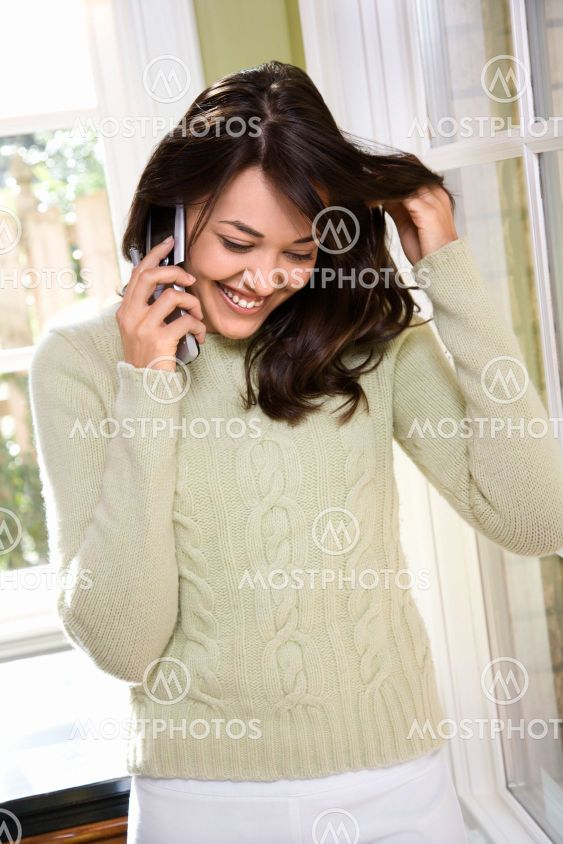 Woman on cellphone smiling.