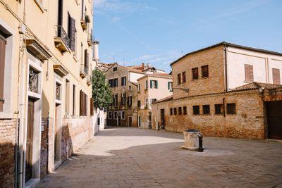 A deserted Venetian street flooded with sunset light. An...