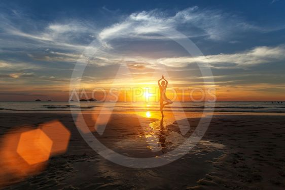 Small silhouette of a woman practicing yoga on sea beach...