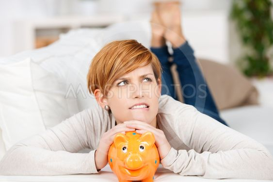 Woman With Piggy Bank While Lying On Sofa