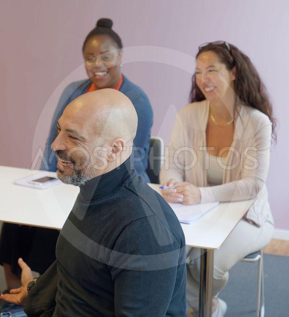 Glada elever med olika etnicitet i klassrum lyssnar på...