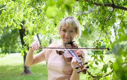 The Russian woman plays a violin in the park in the summer.