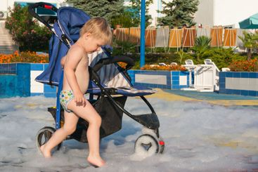 A little blond boy rides a stroller on foam after a foam...