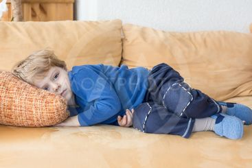 Tired toddler boy laying on couch