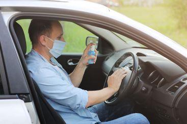 Spraying antibacterial sanitizer spray on steering wheel...